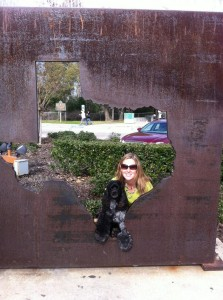 Photo of Meredith with her cockerspaniel posing behind a negative space sculpture of Texas.
